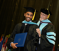 Student and faculty member at graduation ceremony