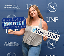 Student holding admitted sign