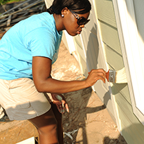 Student painting a house