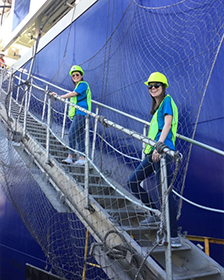 Two students boarding a container ship