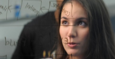female student looking at computer code written on transparent glass