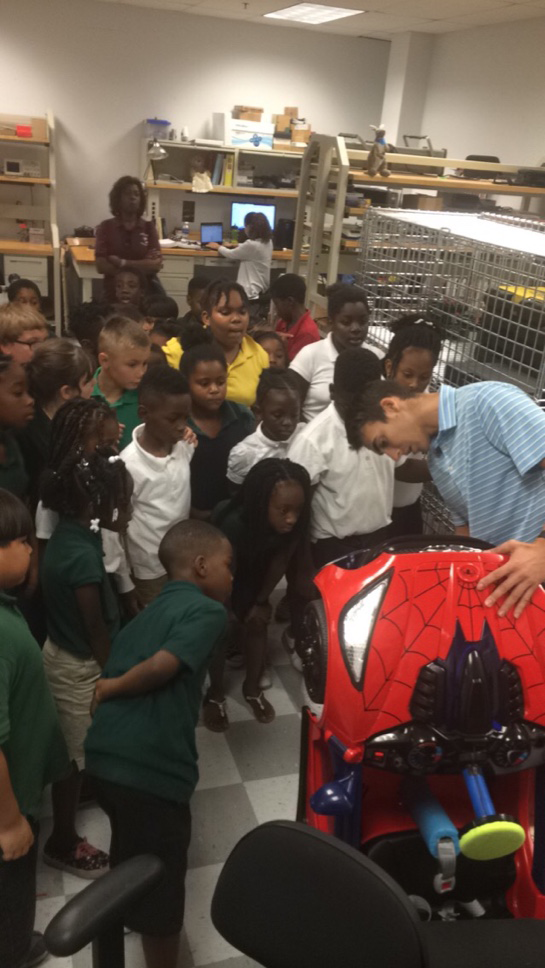 classroom of kids looking at a spiderman car
