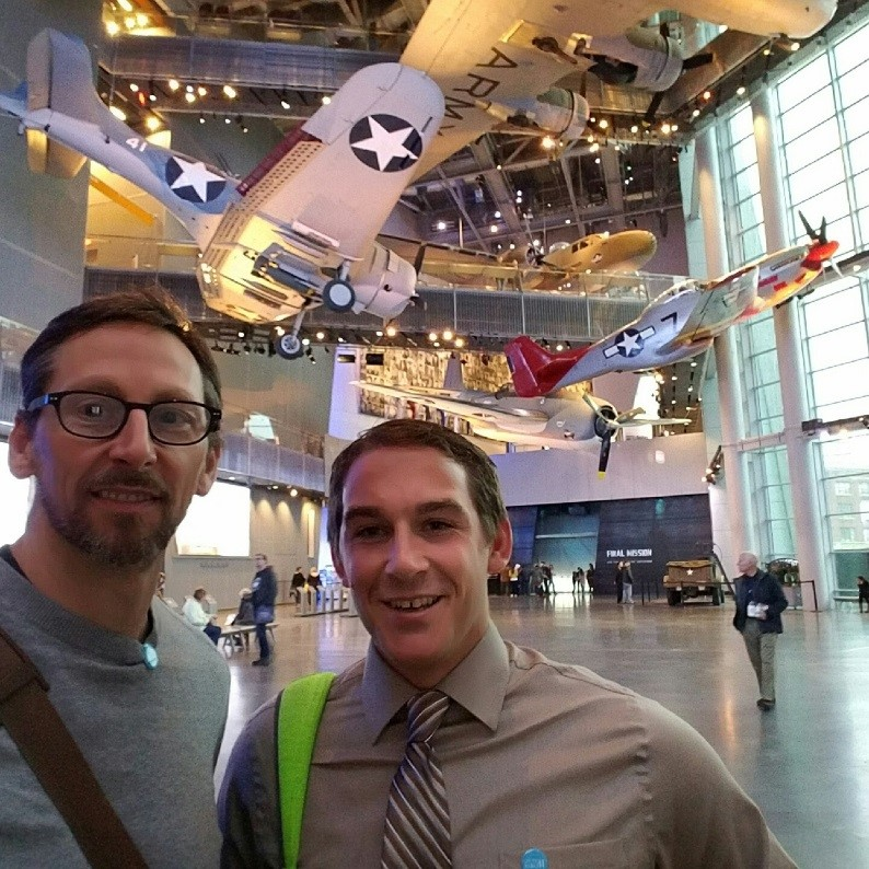 two men in a museum with an airplane in the background