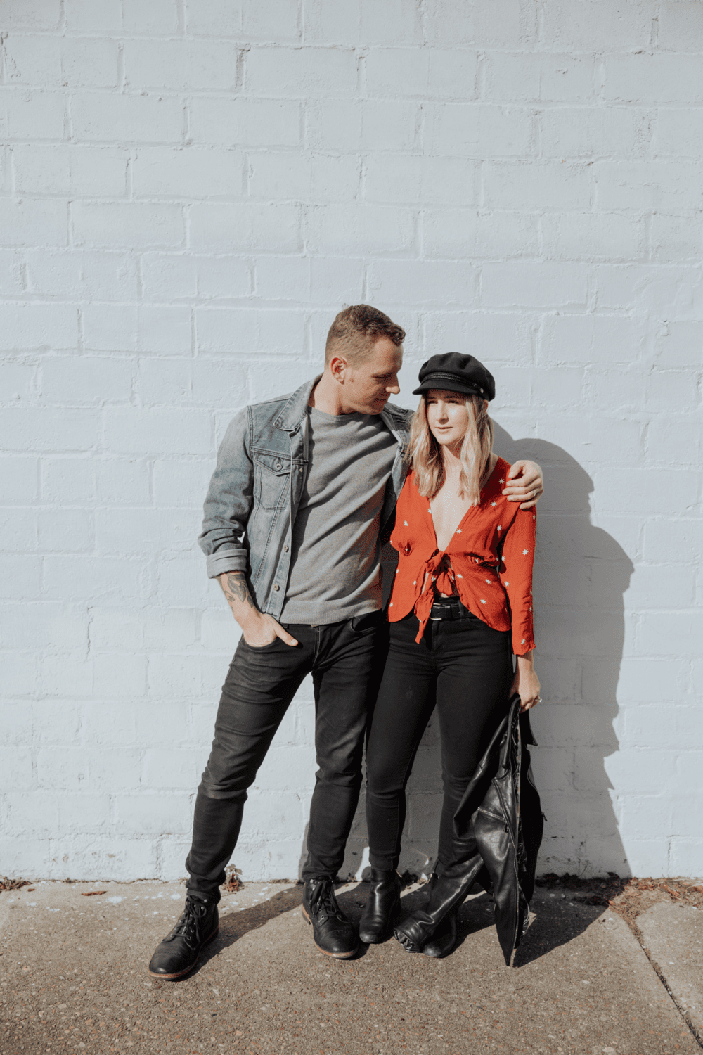 Guy Barnhart and Kayla Beckmann Barnhart posing in front of a brick wall