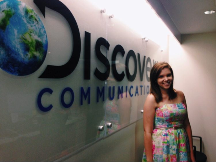 Madison Geery in front of the discovery communications sign