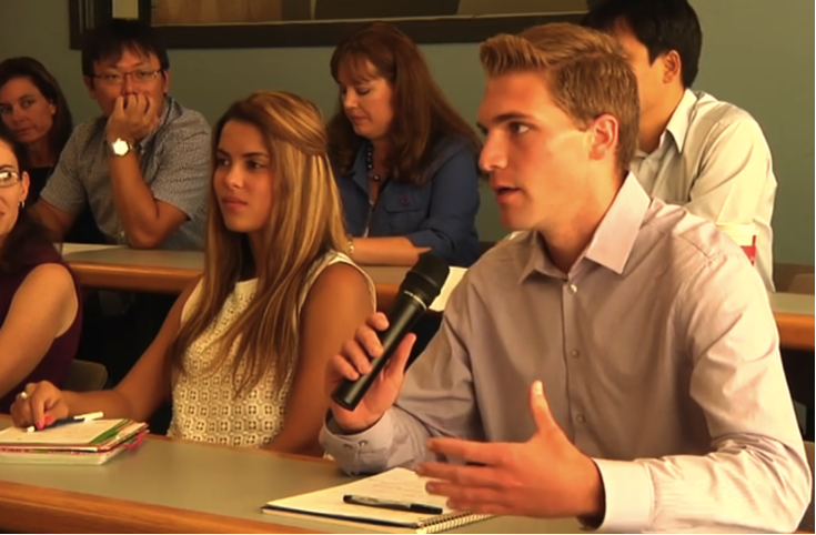 student speaking in class on a microphone
