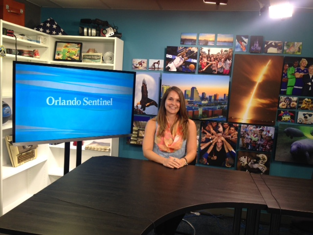 Emilee Speck smiling by a tv that reads orlando sentinel