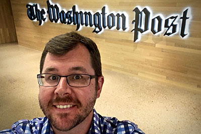 Robert Davis in front of the washington post sign