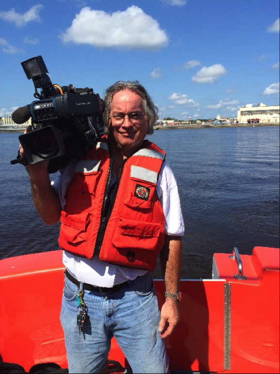 Ken Thomas holding a camera on a boat and wearing a life jacket