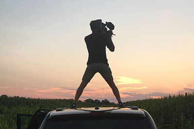 man standing on his car with a camera as the sun sets