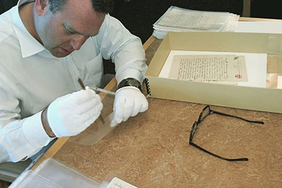 Professor handling a very old book with gloves on a desk