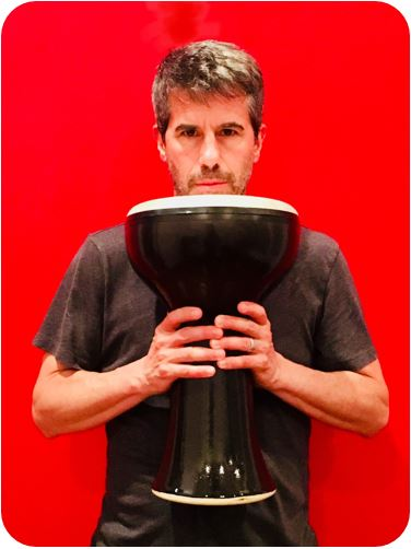 Kenneth Every standing against a red wall with a timpani