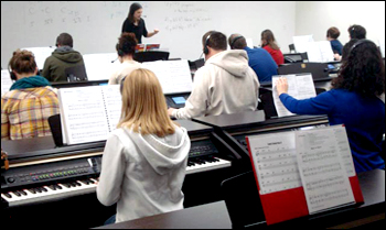 Students playing keyboards in music lab