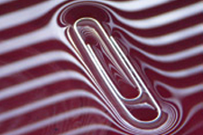 a paperclip sinking in red shiny liquid