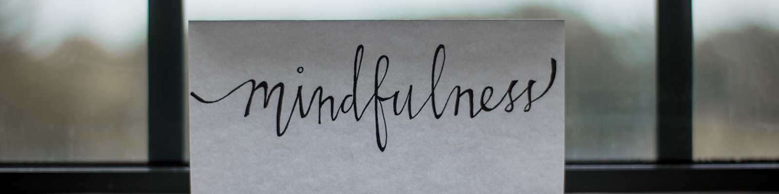card with the word mindfulness laying against a window