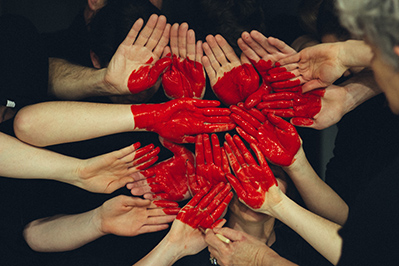 hands united together to create a red painted heart on their palms.