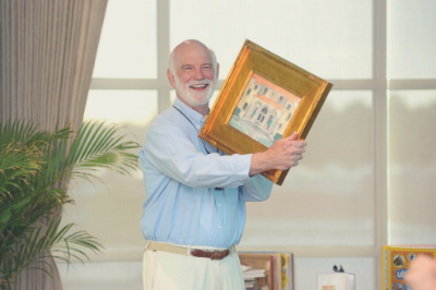 Gilchrist Berg holding a framed painting of a building