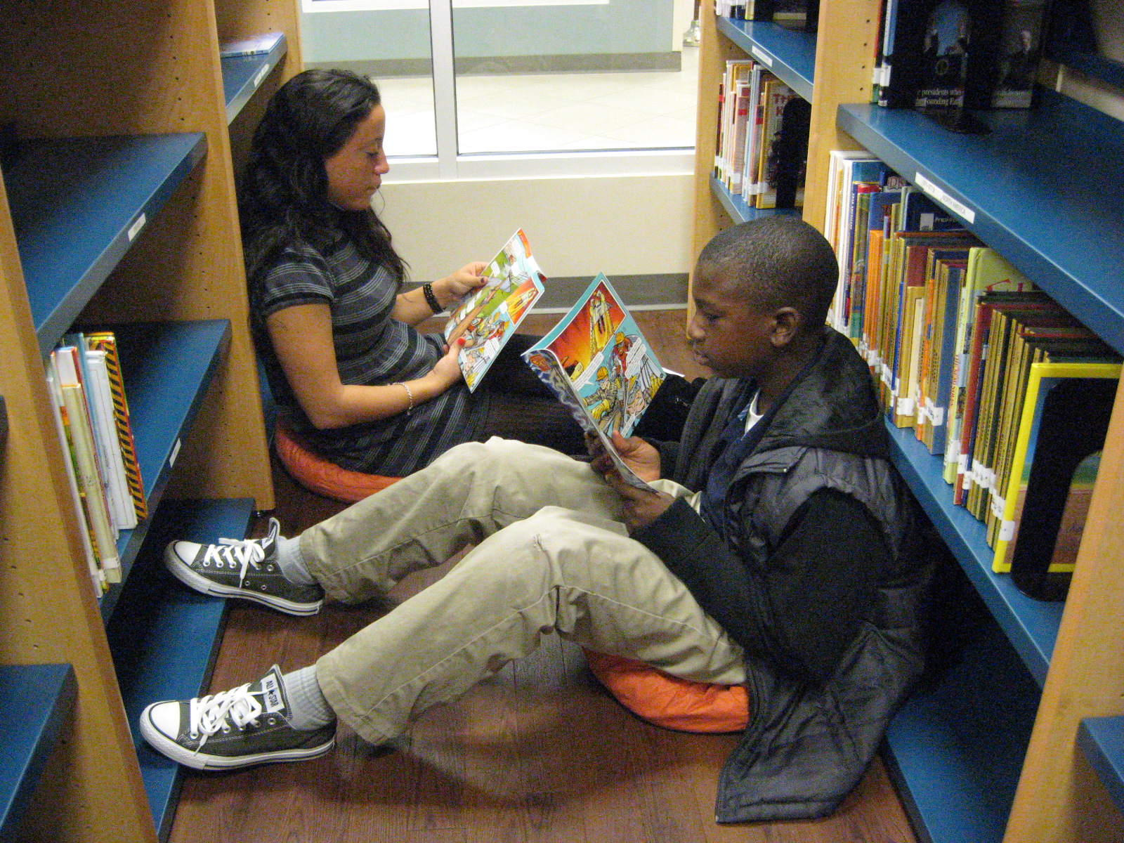 two students reading in the stacks of a library