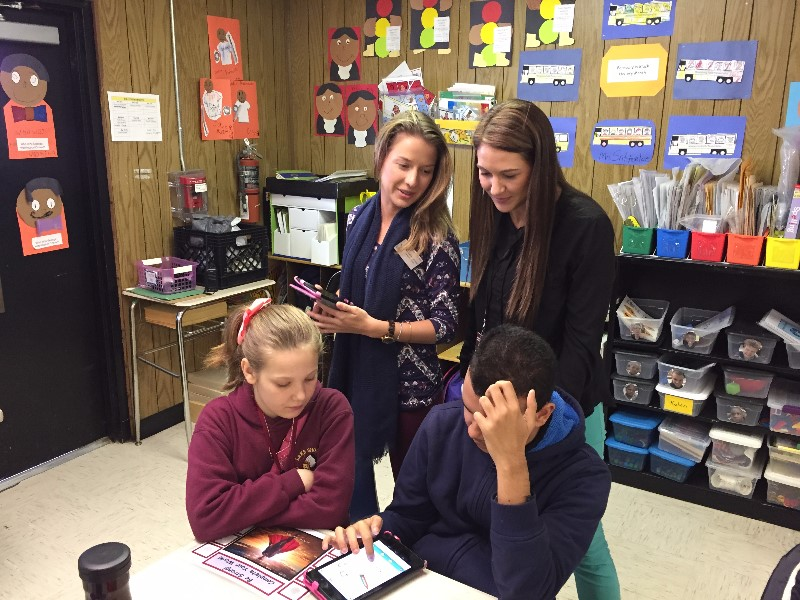teachers overlooking students learning on an electronic pad