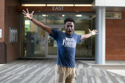 excited student wearing unf shirt in the student union plaza with mouth open and arms raised