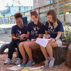 three young women sitting and working together on a project outside