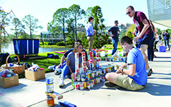 Students sitting on a campus sidewalk, counting cans of food for a food drive.
