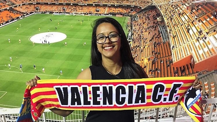 Girl holding Valencia C.F. banner in stadium.
