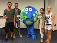 students posing with a globe mascot