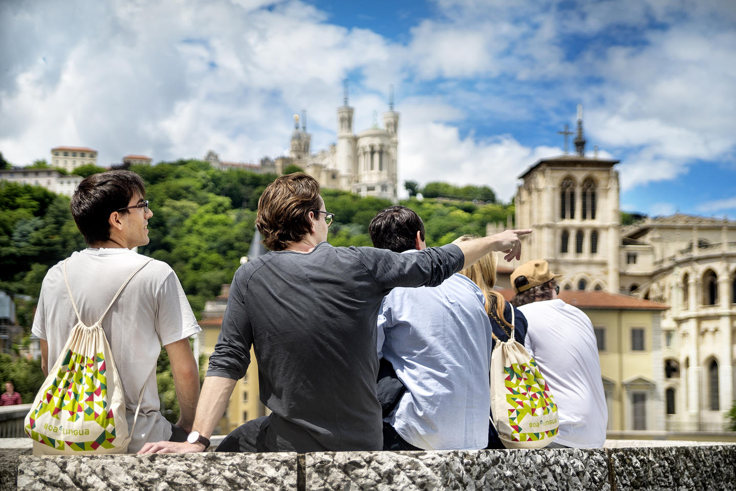 students sitting and looking at the horizon over a city