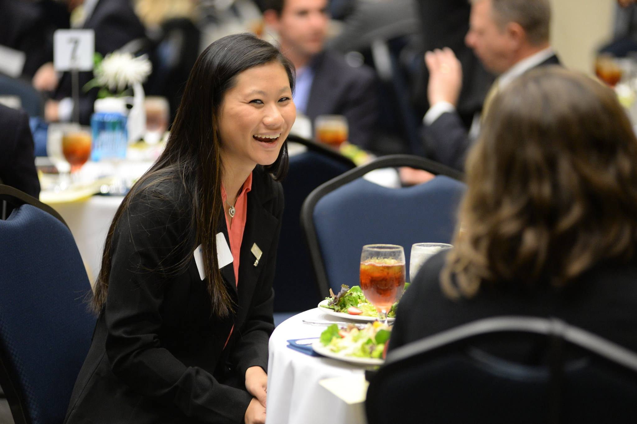 Woman talking with drink in hand at networking event
