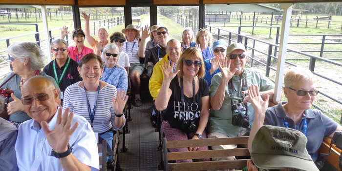 A large group of OLLI members waving while on an Ed2Go trip