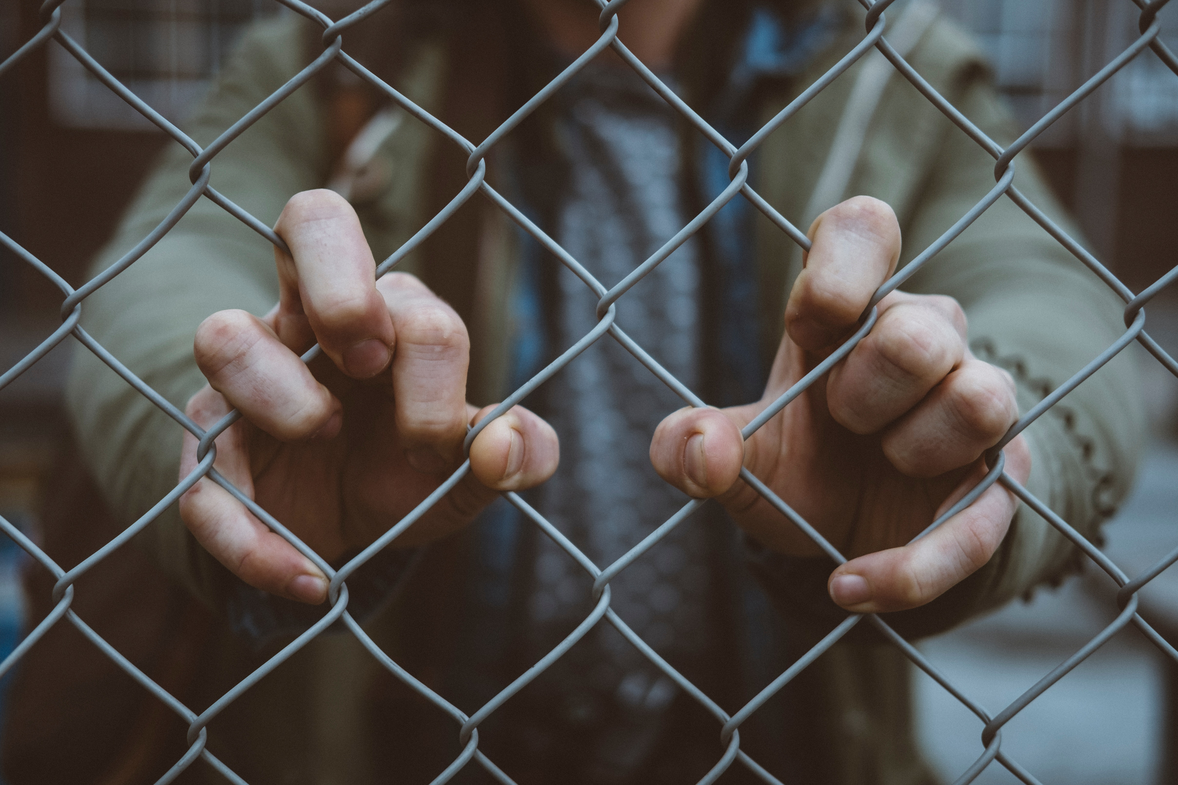 Closeup of hands holding a fence