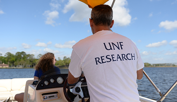 Faculty and student in a boat with UNF Research tshirt on