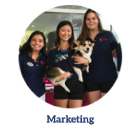 Marketing program link -Three female student holding a puppy and smiling at the camera