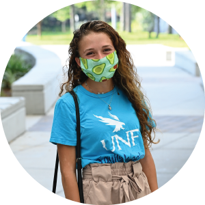 Female in bright blue UNF shirt wearing an face mask that has avocados on it