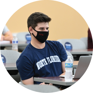 Male student in a UNF tshirt and a face mask sitting in class