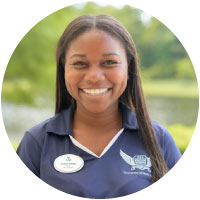 swoop squad member keniya smiling at camera with unf blue polo
