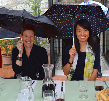 Student and faculty under umbrellas at a cafe