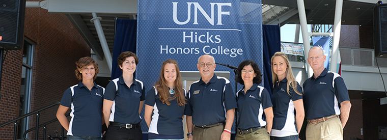 Staff in polo shorts standing in front of a Hicks Honors College banner