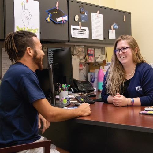 Financial aid advisor speaking with a male student about loans