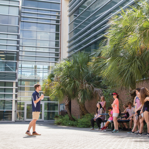 Tour guide giving tour in front of the Biology building