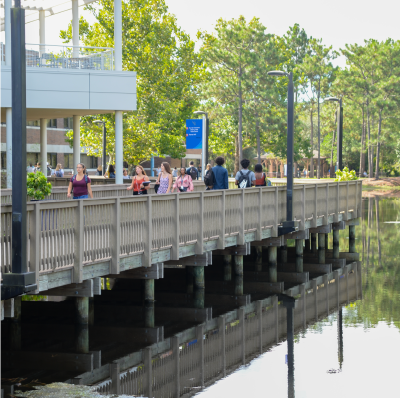 People on UNF campus walking on a boardwalk by lake