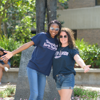 Two students wearing UNF t-shirts smiling with excited arm poses