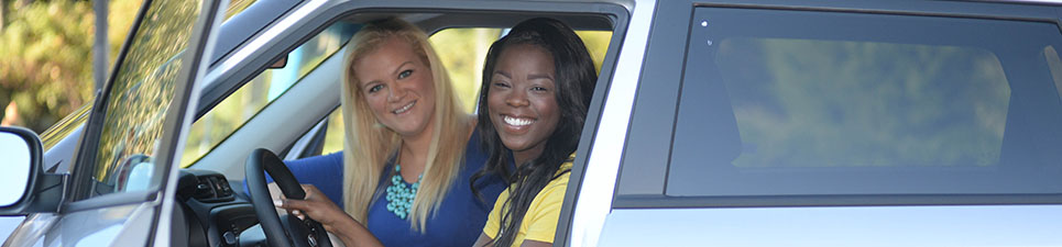 Two smiling students sitting in parked vehicle facing the camera