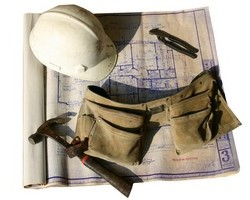 work belt, hard hat, blue prints and hammer