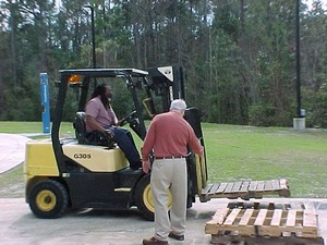 Yellow and black forklift picking up pallets
