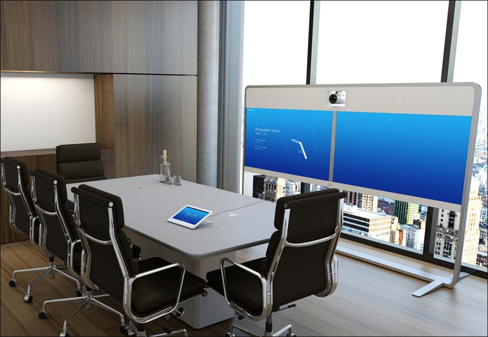 Conference room with table and dual screen telepresence monitors.