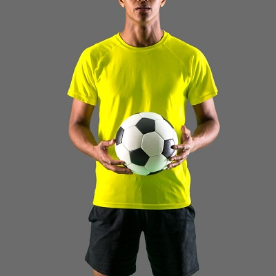 man in a yellow shirt holding a soccer ball