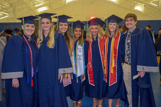 graduates wearing navy caps and gowns with tassels and stolls representing their clubs