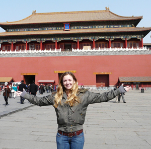 A student posing in front of a landmark in China